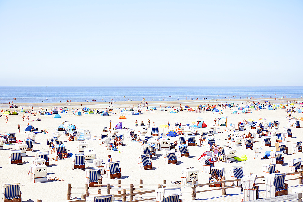 Vast beach with roofed wicker beach chairs on wooden plateaus and people celebrating the summer, Sankt Peter Ording, Schleswig Holstein, Germany, Europe - 1294-99