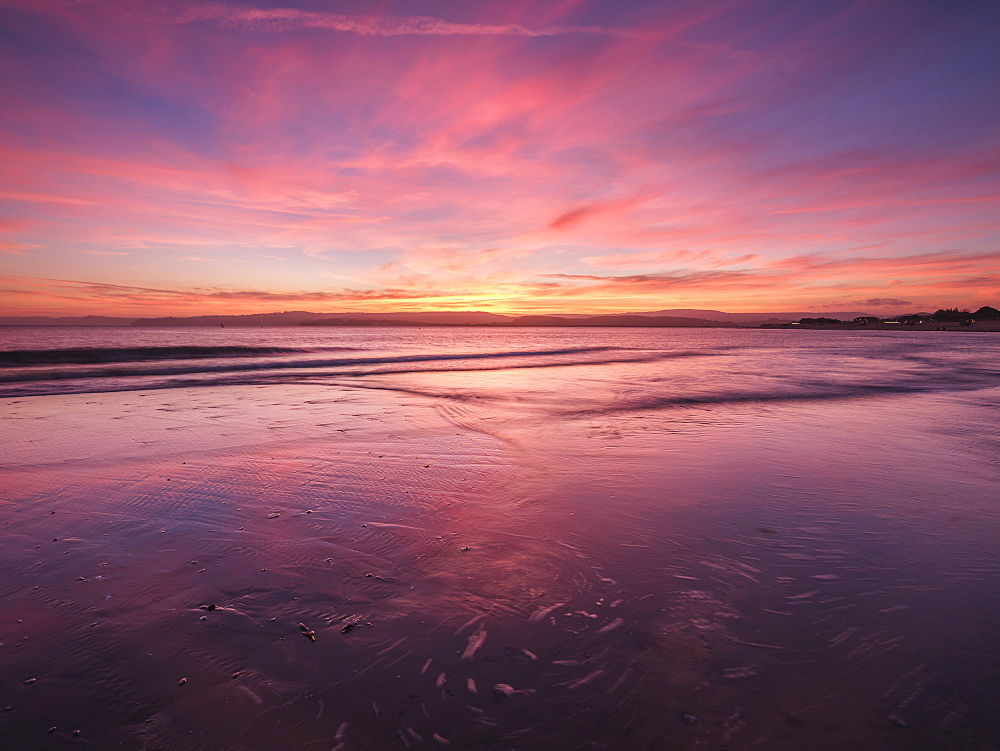 Really strong afterglow and interesting wispy clouds, reflected in the sea at Exmouth, Devon, England, United Kingdom, Europe
