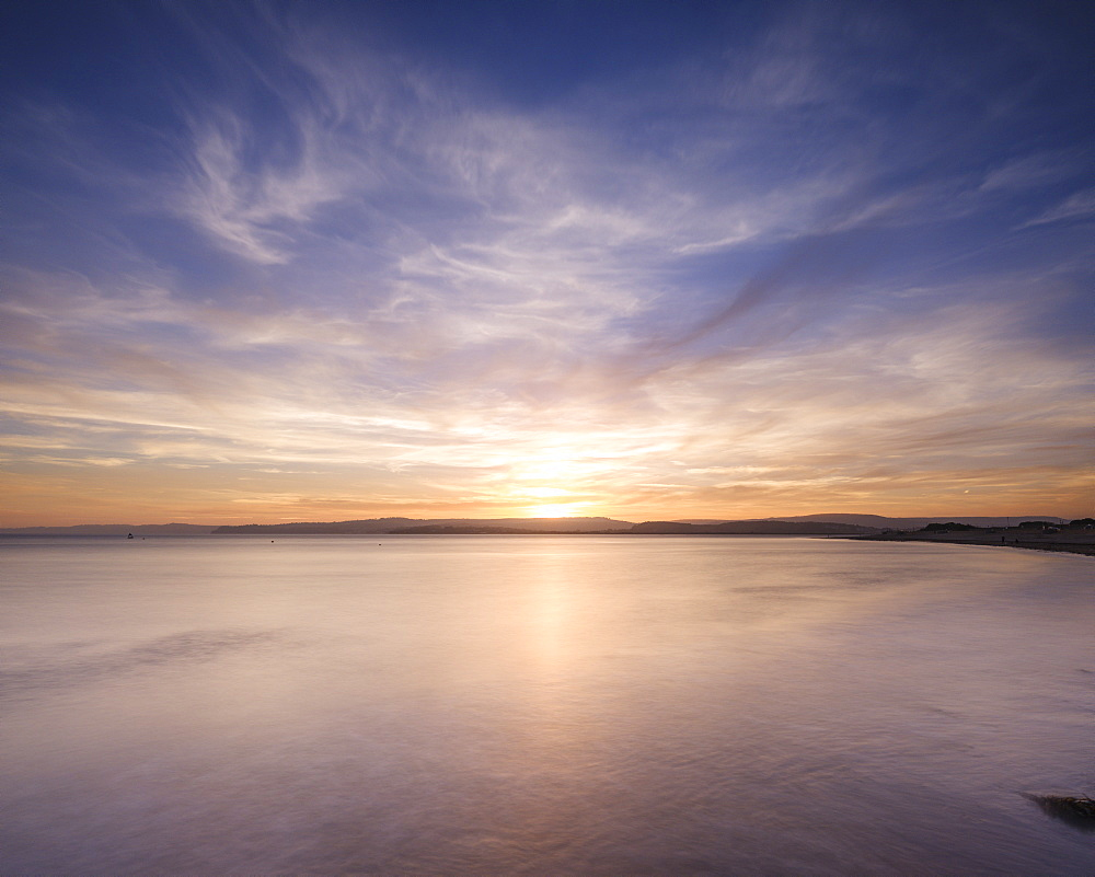 With interesting wispy clouds, the sun sets across the water from Exmouth, Devon, England, United Kingdom, Europe - 1295-106