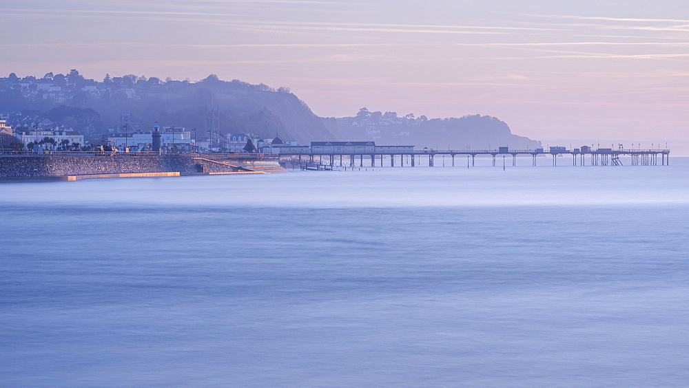 Sun making the sea wall glow on Teignmouth sea front with Teignmouth Pier behind, viewed from Shaldon, Devon, England, United Kingdom, Europe