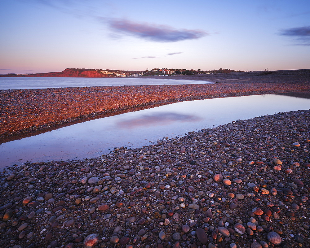 First sunlight falls on Budliegh Salterton with pebbles on the curving beach from Otter Mouth, Budleigh Salterton, Devon, England, United Kingdom, Europe - 1295-25