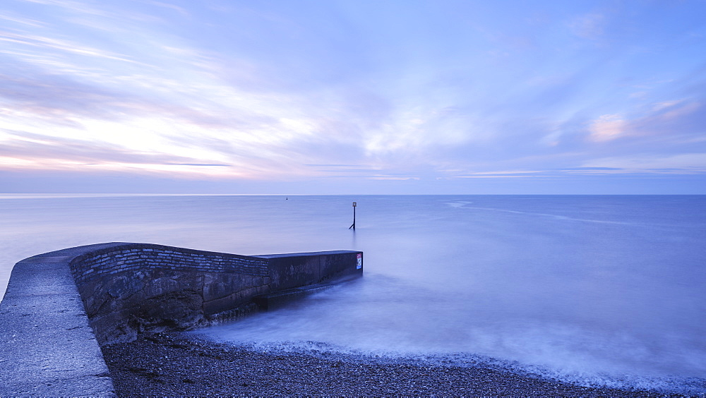 Dawn clouds and soft sea beyond the breakwater at Sidmouth, Devon, England, United Kingdom, Europe