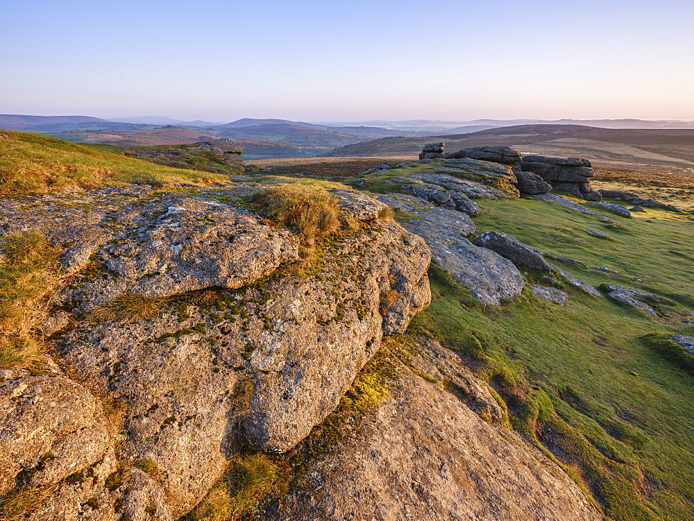 Warm sunlight on the granite summit of Saddle Tor in Dartmoor National Park, Bovey Tracey, Devon, England, United Kingdom, Europe
