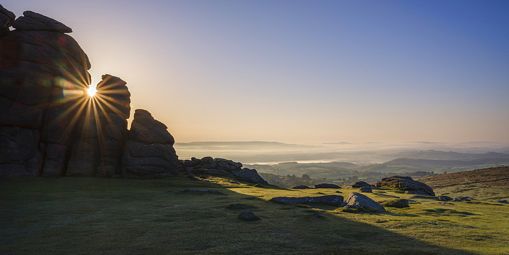 Sun breaks through a gap in granite rocks at Haytor in Dartmoor National Park, Bovey Tracey, Devon, England, United Kingdom, Europe - 1295-76
