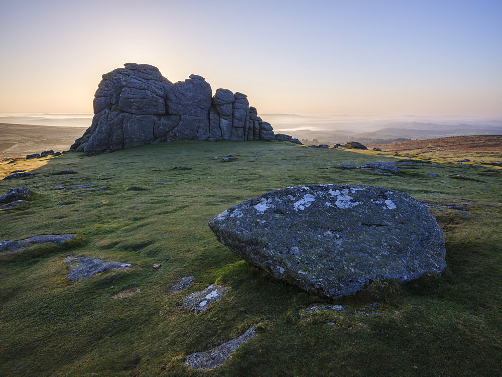 Sun behind granite rocks at Haytor in Dartmoor National Park and distant mist in the Teign Valley, Bovey Tracey, Devon, England, United Kingdom, Europe - 1295-78
