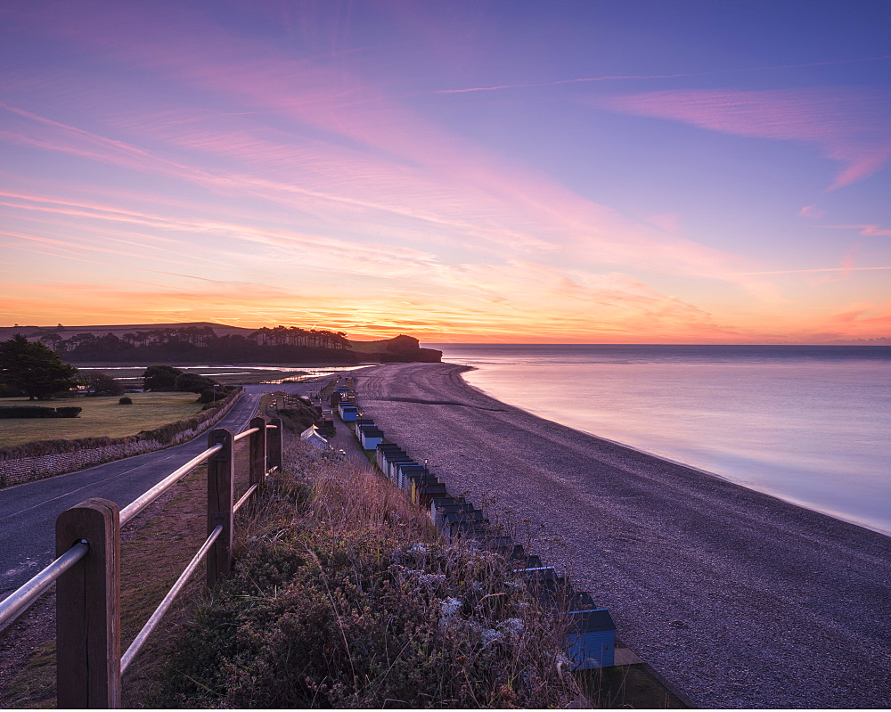 Colourful dawn with sweep of the shoreline, beach huts, pebbles and the cliff of Otter Head at Budleigh Salterton, Devon, England, United Kingdom, Europe - 1295-88