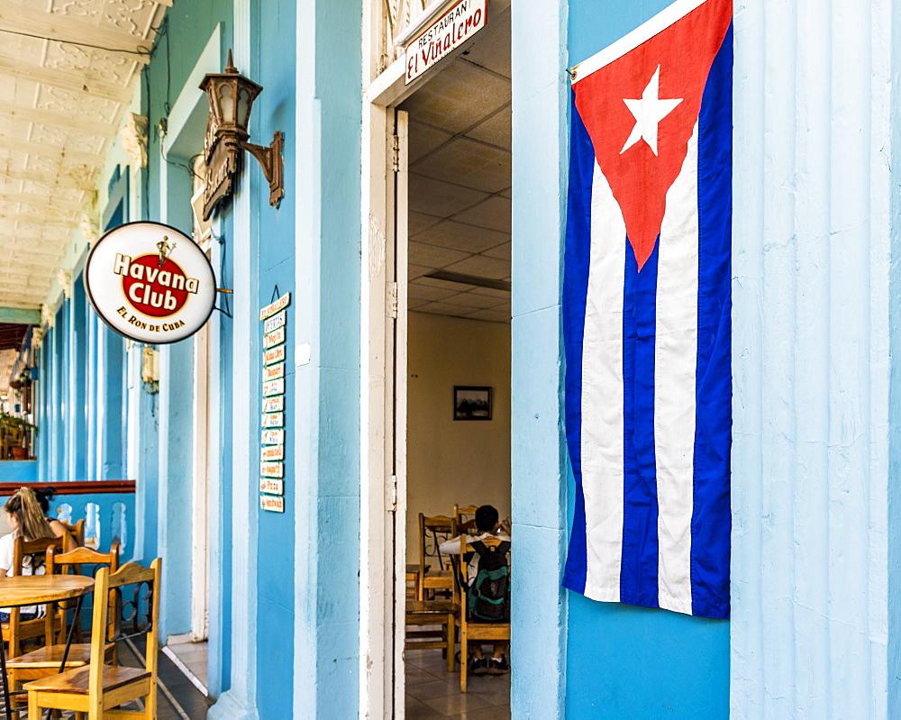 A Cuban flag outside a restaurant in Vinales town, Vinales, Pinar del Rio, Cuba, West Indies, Caribbean, Central America