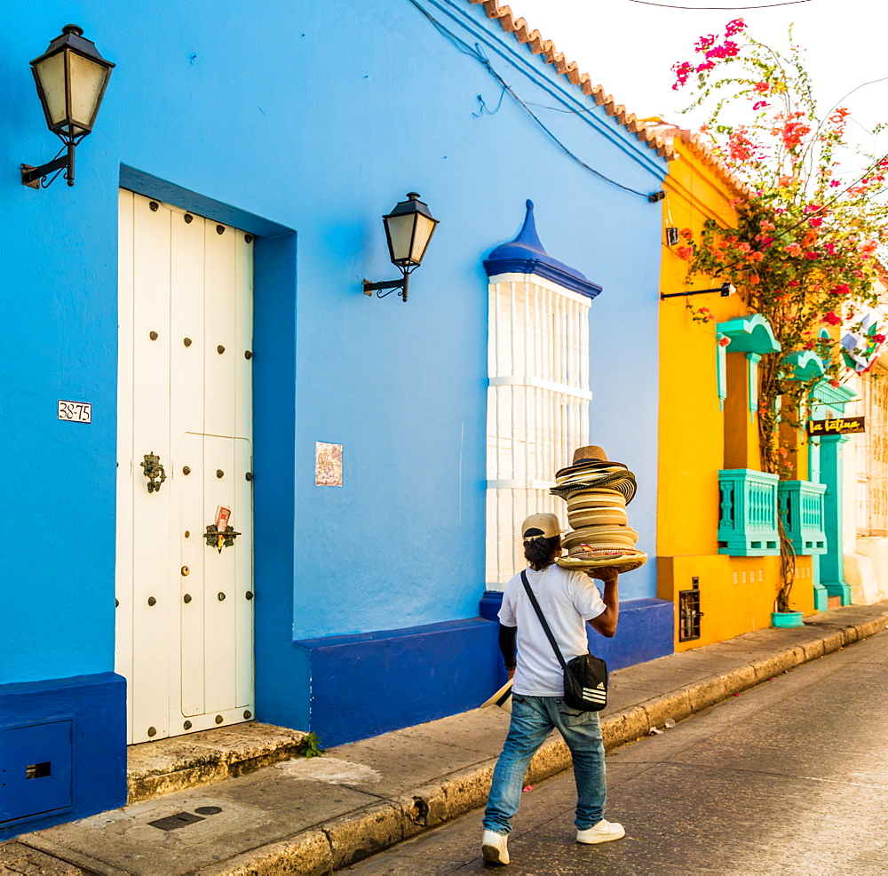 A street vendor walking past a colourful building in the old town in Cartagena, Colombia, South America.