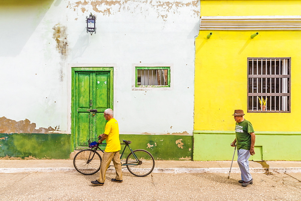 Local men walking past typically colourful colonial architecture in Trinidad, Cuba, Caribbean, Central America.