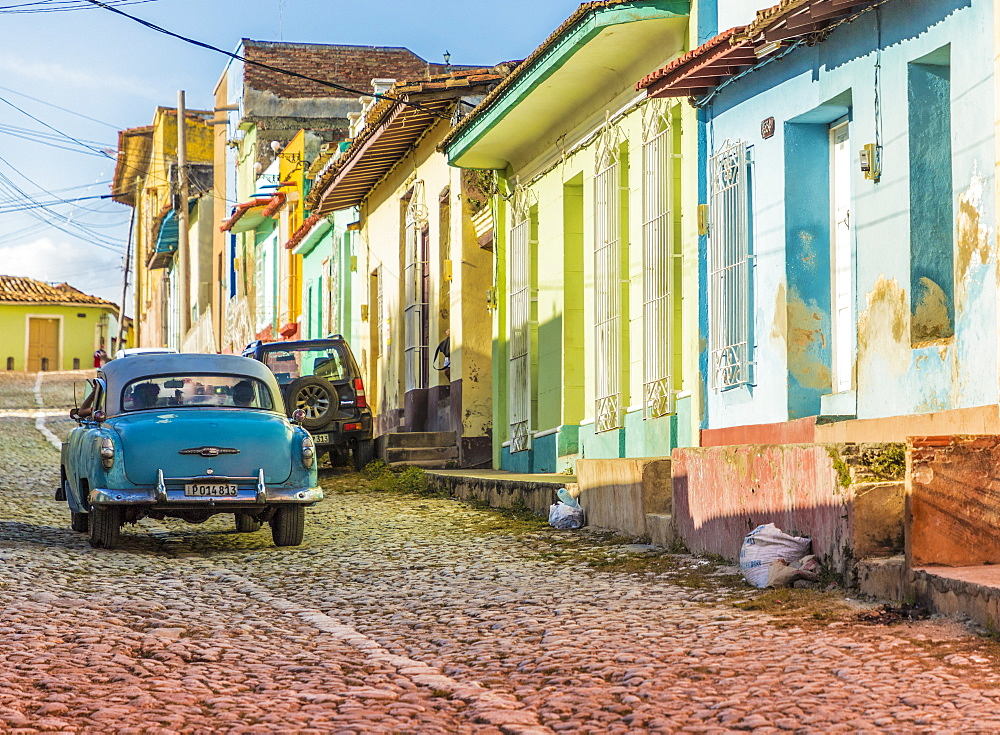 A car in a colourful colonial street in Trinidad, Cuba, Caribbean, Central America.