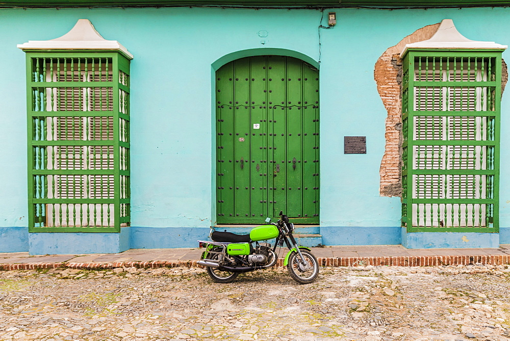 A motorbike in a typically colourful colonial street in Trinidad, Cuba, Caribbean, Central America.