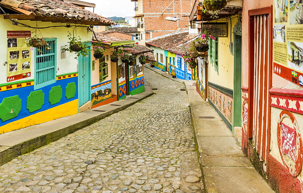 A typically colourful street with buildings covered in traditional local tiles in the picturesque town of Guatape, Colombia, South America