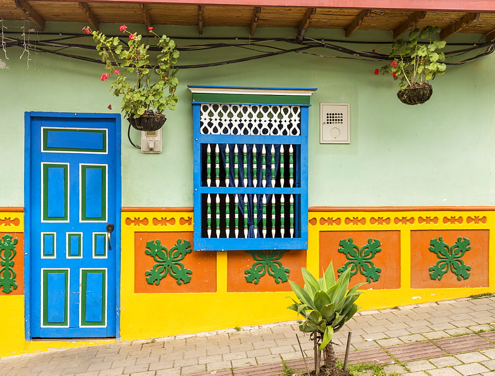 The facade of a colourful building covered in traditional local tiles, in the picturesque town of Guatape, Colombia, South America