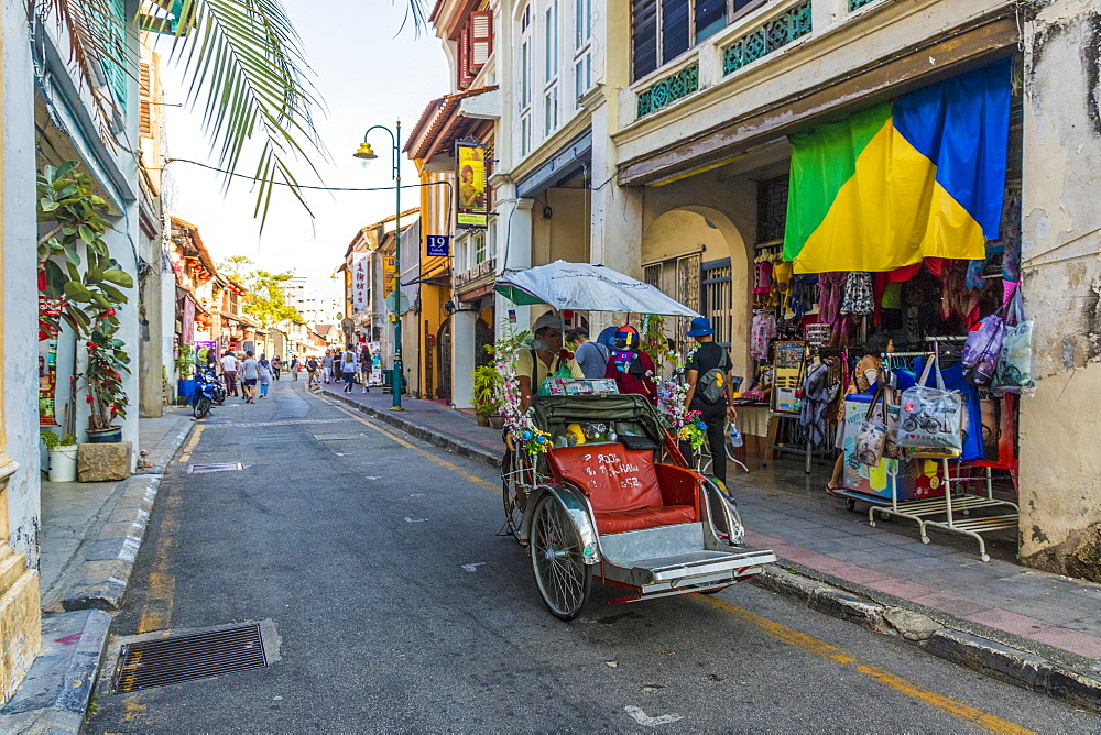 A local rickshaw (tuk tuk) driver in a colourful street scene in George Town, Penang Island, Malaysia, Southeast Asia, Asia