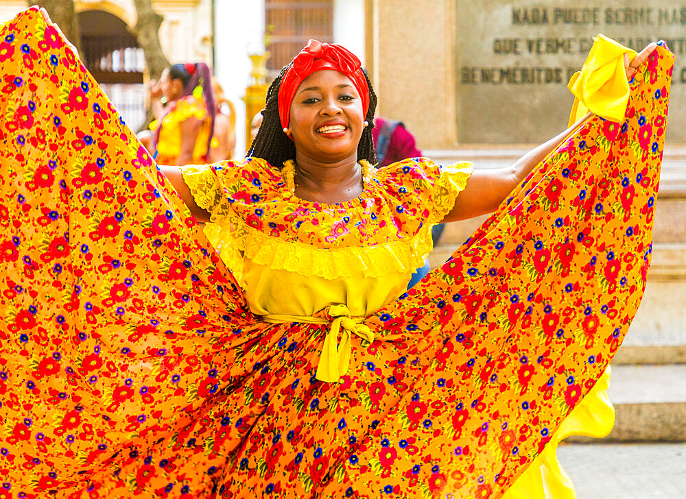A woman wearing colourful traditional clothing dancing in Cartagena de Indias, Colombia, South America.