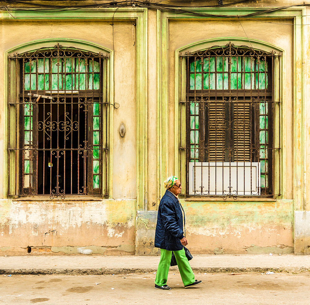A local man passing a beautifully aged colourful building in Havana, Cuba, West Indies, Caribbean.