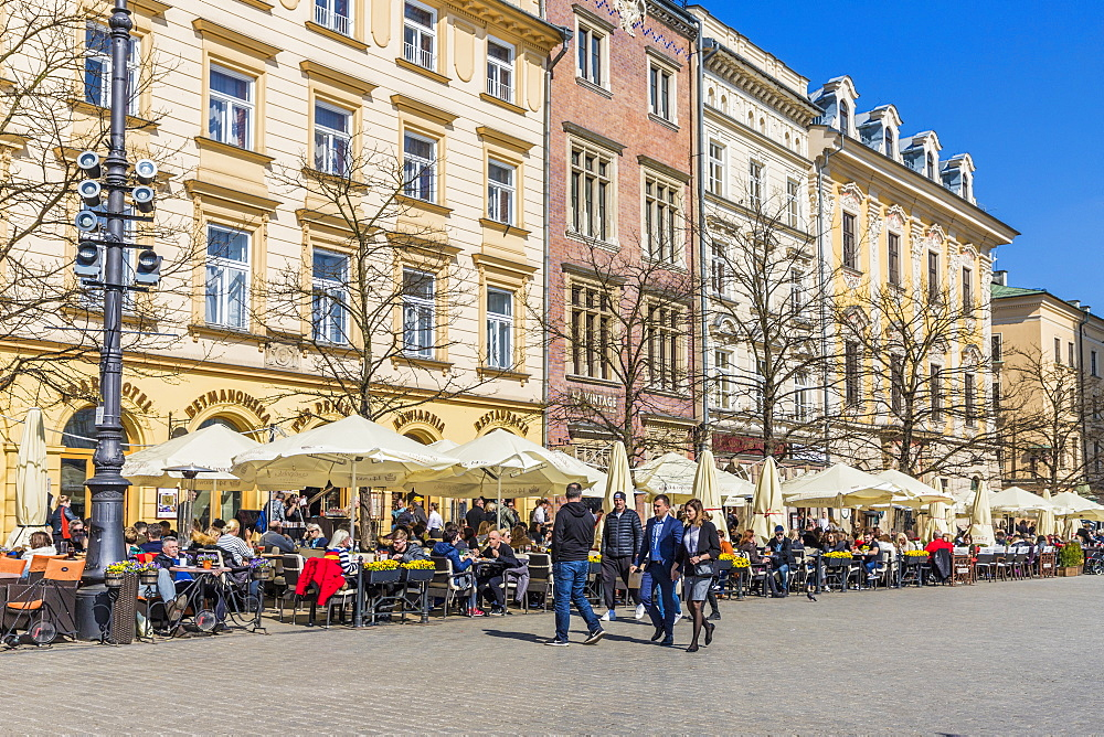 A cafe scene in the main square, Rynek Glowny, in the medieval old town, UNESCO World Heritage Site, Krakow, Poland, Europe