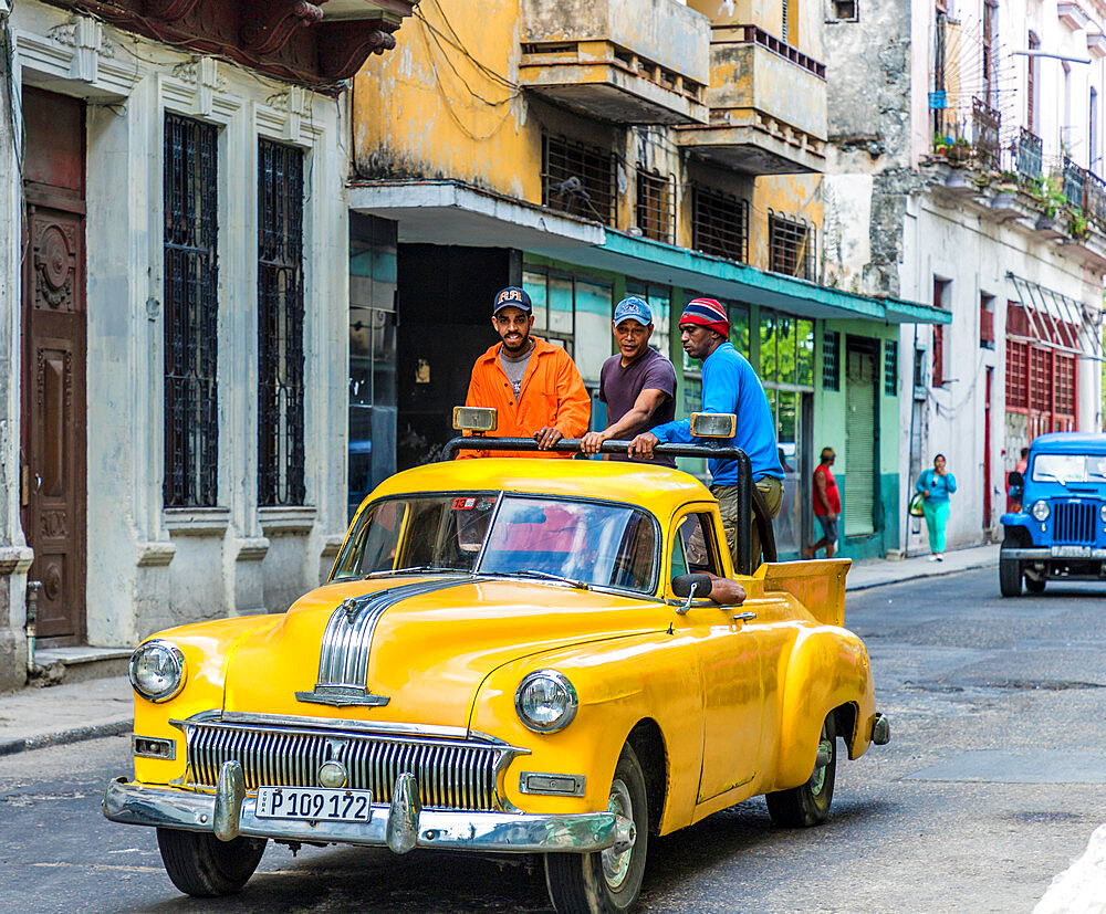 Local men riding in a vintage car in Havana, Cuba, West Indies, Caribbean.