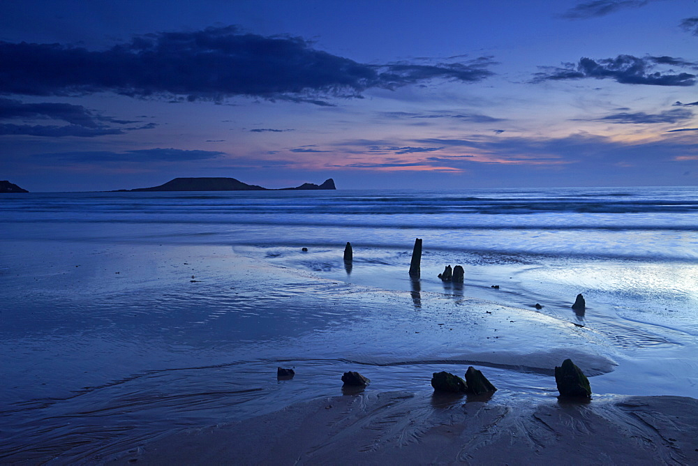 Dusk over the wreck of the Helvetia and Worms Head at Rhossili Bay, Gower, Wales, United Kingdom, Europe
