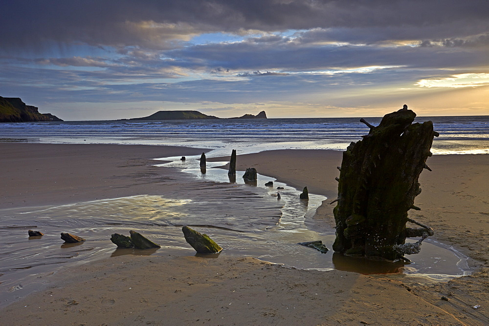 Sunset over the wreck of the Helvetia and Worms Head at Rhossili Bay, Gower, Wales, United Kingdom, Europe