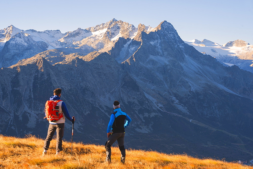 Hikers admiring the mountains in autumn season in Stelvio National Park in Brescia Province, Lombardy, Italy, Europe