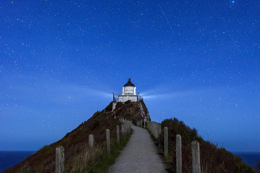 Nugget Point lighthouse under star filled sky, Kaka Point, Otago, South Island, New Zealand, Pacific