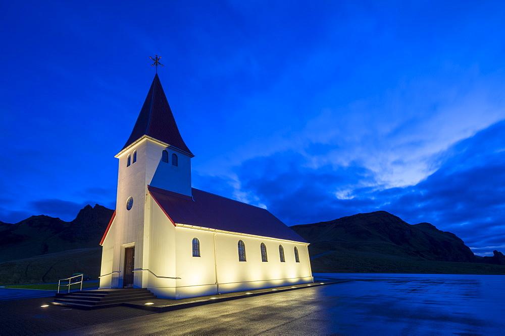 Floodlit church at dawn, near Vik, South Iceland,