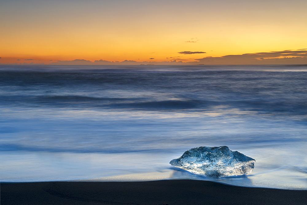 Single Ice formation at sunrise on ice beach at Jokulsarlon, Iceland.