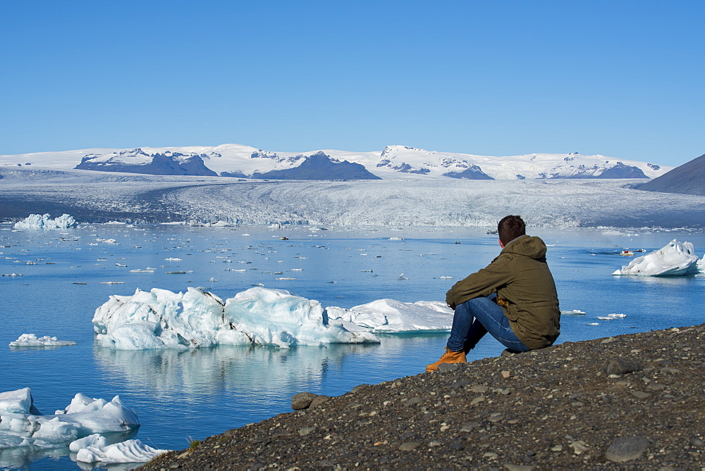 Young male sat admiring the view of Jokulsarlon Glacier Lagoon, South East Iceland, Iceland, Polar Regions