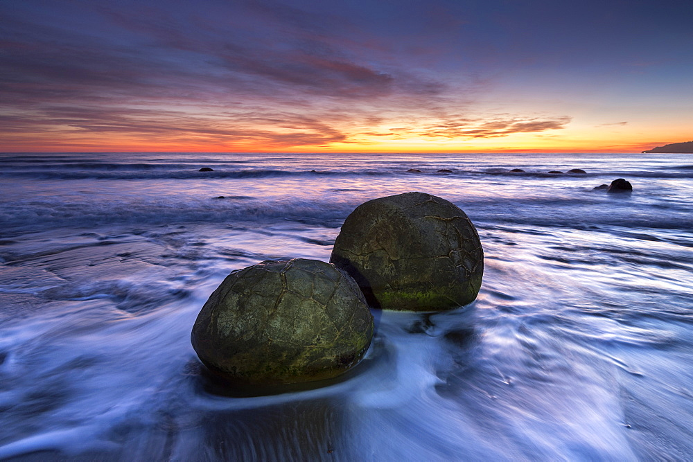 The Moeraki Boulders with dramatic sunrise at Moeraki Beach, Otago, New Zealand