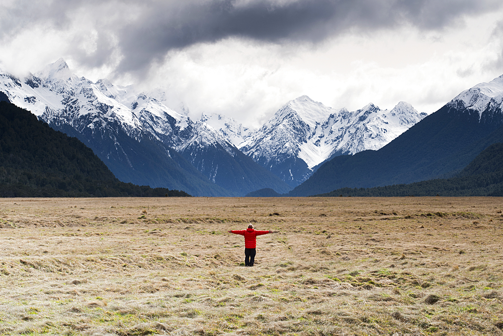 Man in red coat stood holding out his arms looking at snow capped mountains, Fiordland National Park, New Zealand