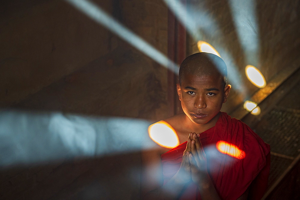 Novice Buddhist monk praying with shafts of light, Bagan, Myanmar (Burma), Asia