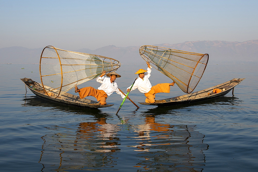 Two Intha leg rowing fisherman holding up fishing nets, Inle Lake, Shan State, Myanmar (Burma), Asia