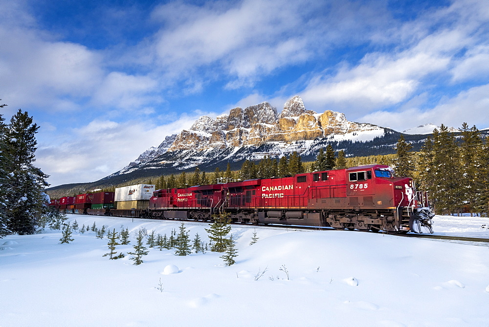 Canadian locomotive passing Castle Mountain in winter, near Banff, Alberta, Canada