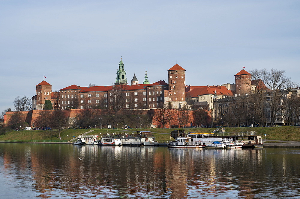 View to Wawel castle, UNESCO World Heritage Site, with restaurant boats moored on Wista (Vistula) River in riverside park, Krakow, Poland, Europe