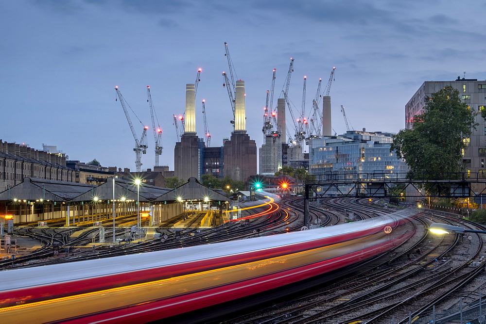 LON 86 Long exposure of passenger train travelling towards Battersea Power Station, London