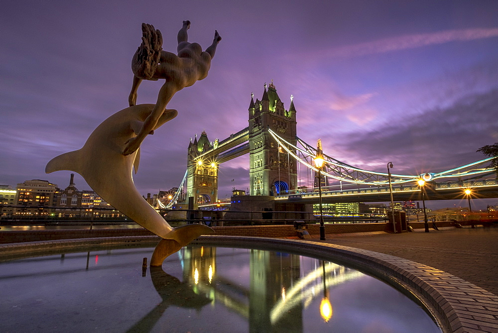 Lon 75 Tower Bridge with the mermaid and dolphin statue at St Katherines Dock at night, London.
