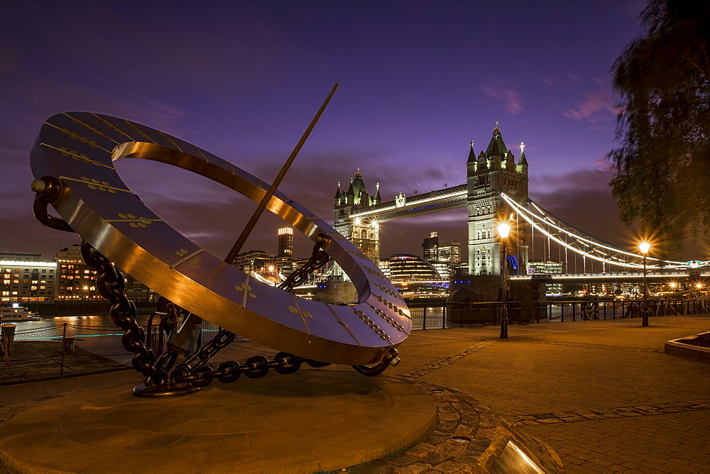 LON 73 Tower Bridge with the sundial statue at St Katherines Dock at night, London.