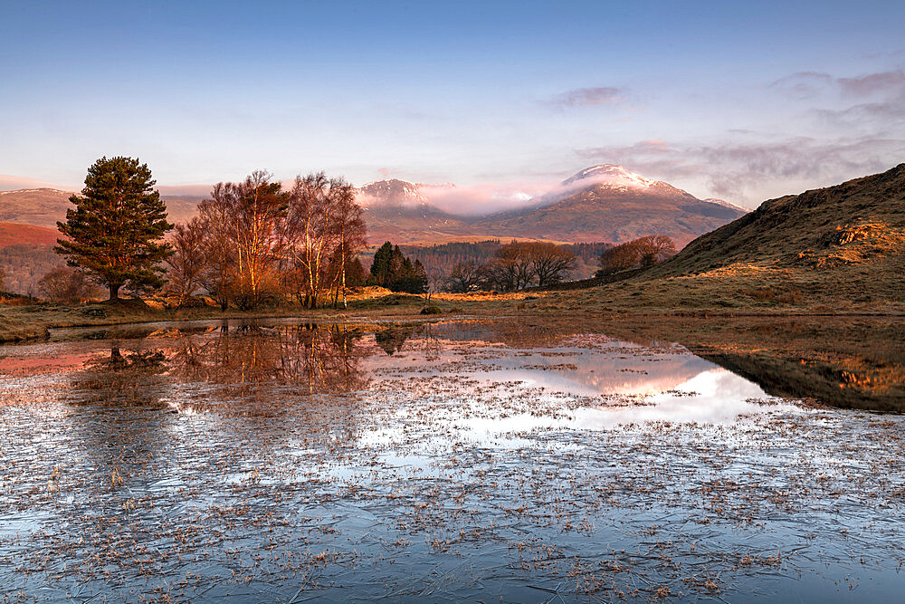 Partially frozen Kelly Hall Tarn and view of Coniston Old Man, Lake District, Cumbria