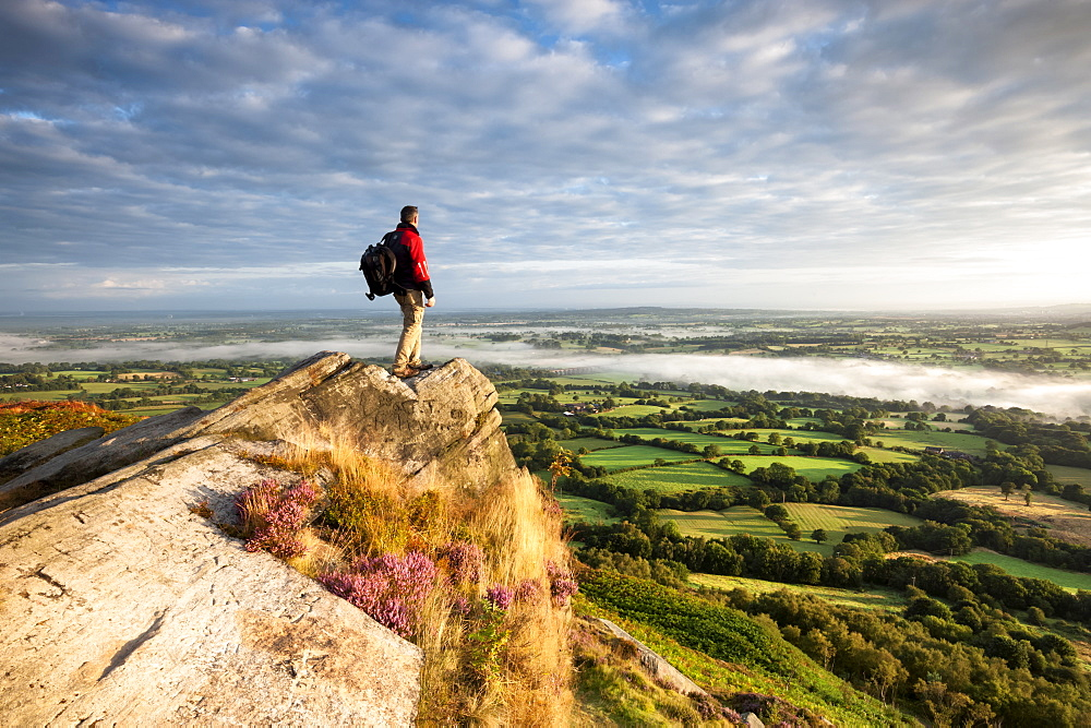 Hiker on rock above Cheshire Plains, Cloudside near Congleton, Cheshire, England, United Kingdom, Europe