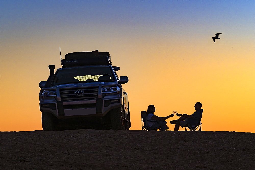 Couple toasting a sunset next to their off road vehicle, Dampier, Western Australia