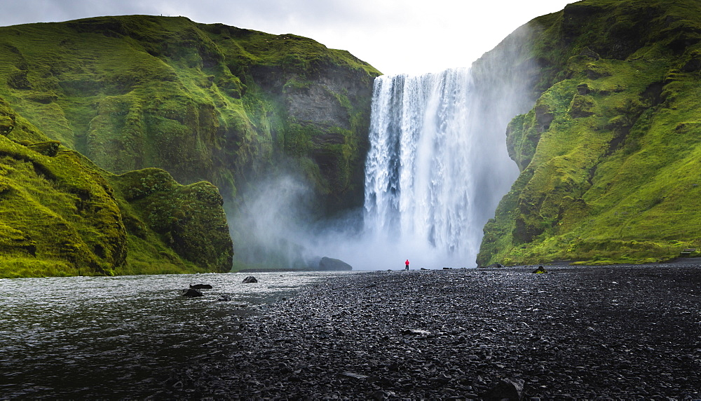 Visitor dwarfed by plunging waters of Skogafoss, Iceland's most iconic waterfall, situated on the Skoga River, Southern Region, Iceland, Polar Regions