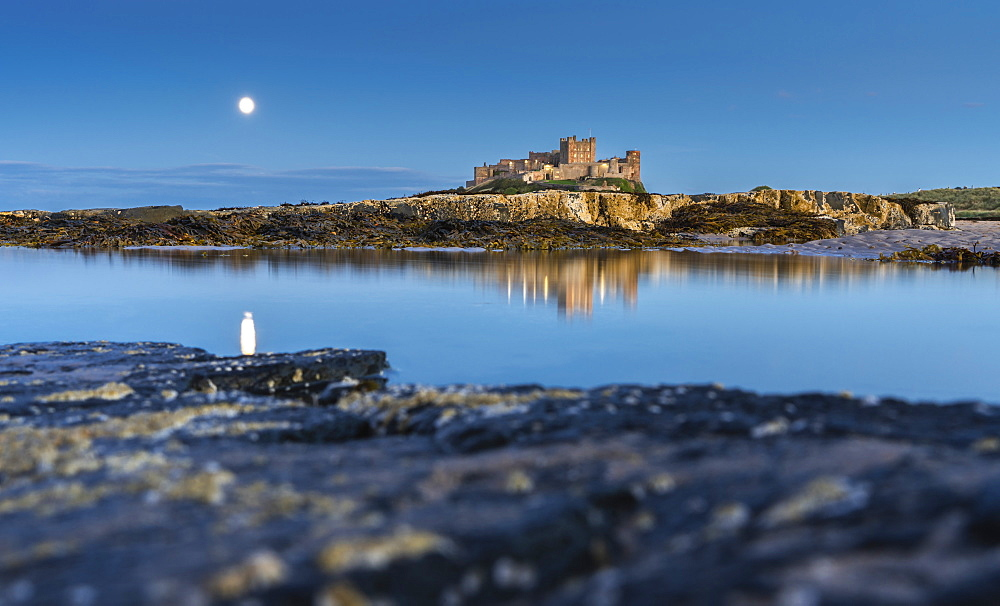 Moonlit Bamburgh Castle reflected in still water at dusk, Bamburgh, Northumberland, England, United Kingdom, Europe