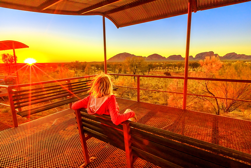 Tourist woman sitting on a bench at platform dune viewing area and looking Mount Olga in Uluru-Kata Tjuta National Park at orange sunset sky. Australian outback in Northern Territory, Australia