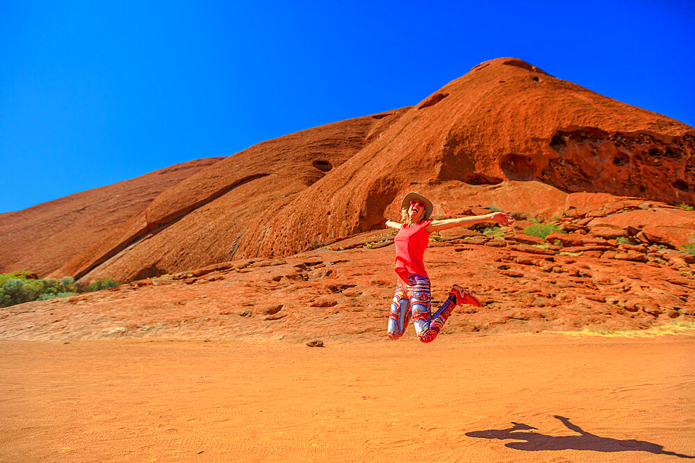Tourist woman jumping at Ayers Rock in Uluru-Kata Tjuta National Park. Happy traveler enjoying along Lungkata walk connecting Kuniya walk to Mala carpark. Tourism in Northern Territory, Australia.