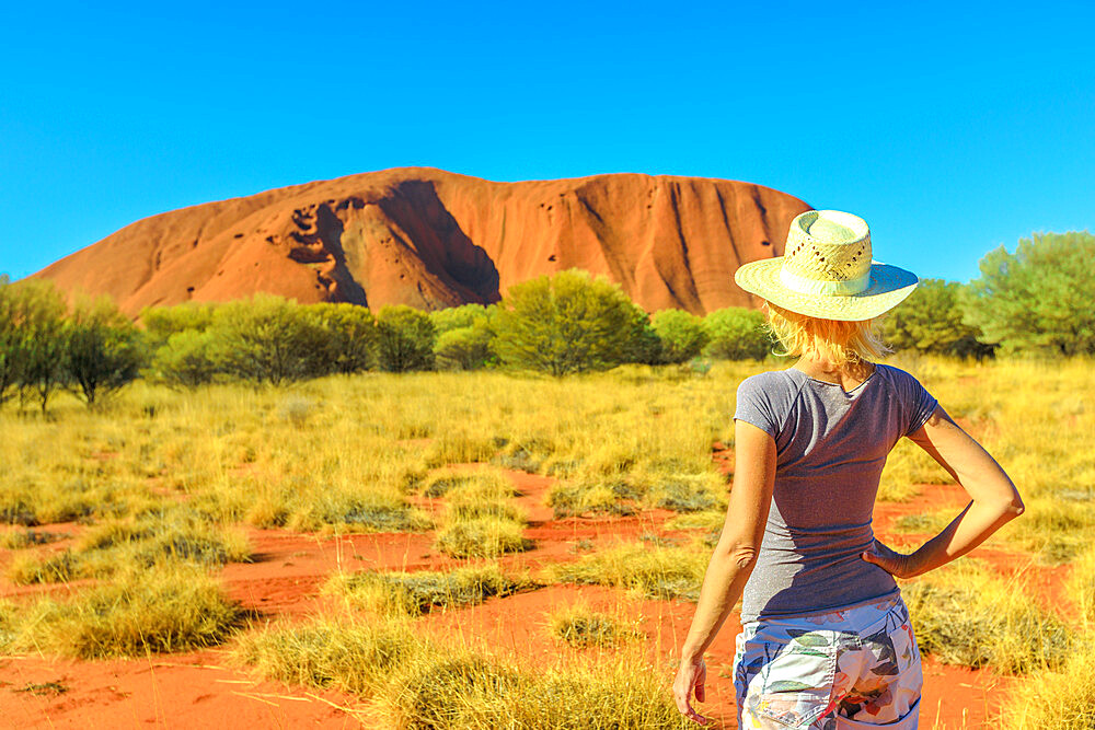 Tourism in Northern Territory, Central Australia. Lifestyle tourist woman in hat looks Uluru Ayers Rock in Uluru-Kata Tjuta National Park. Caucasian traveler in Australian outback in dry season.