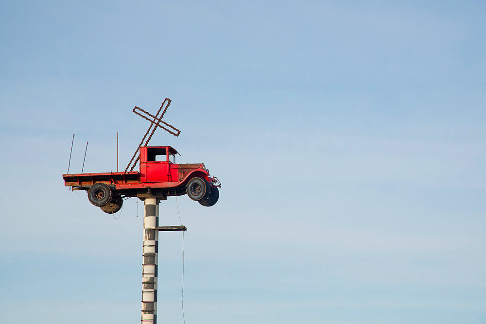 Vintage truck with a cross in the back suspended on a pole in New Mexico, United States of America, North America