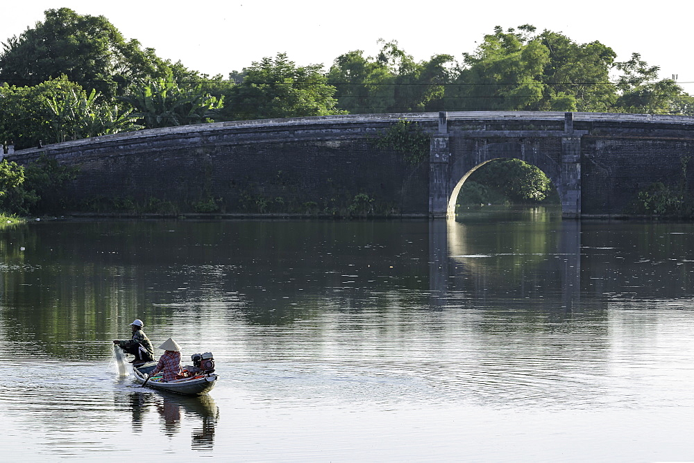 A man and woman fishing from a small boat in the moat around the Citadel in Hue, Vietnam, Indochina, Southeast Asia, Asia