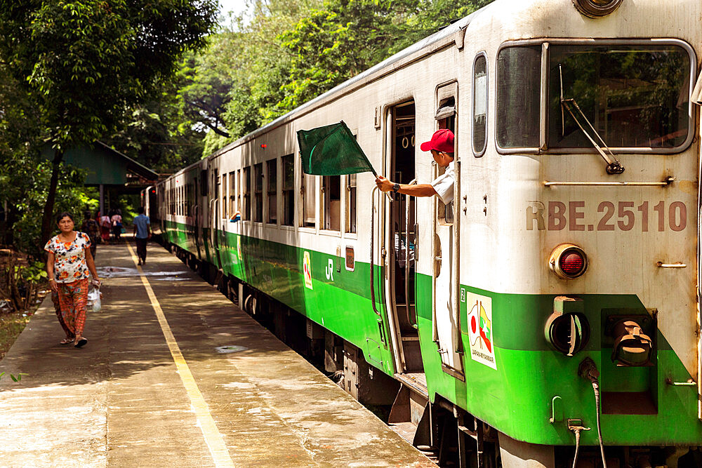 A passenger train at Lanmadaw station with train conductor waving a green flag and a passenger on the platform, Yangon (Rangoon), Myanmar (Burma), Asia