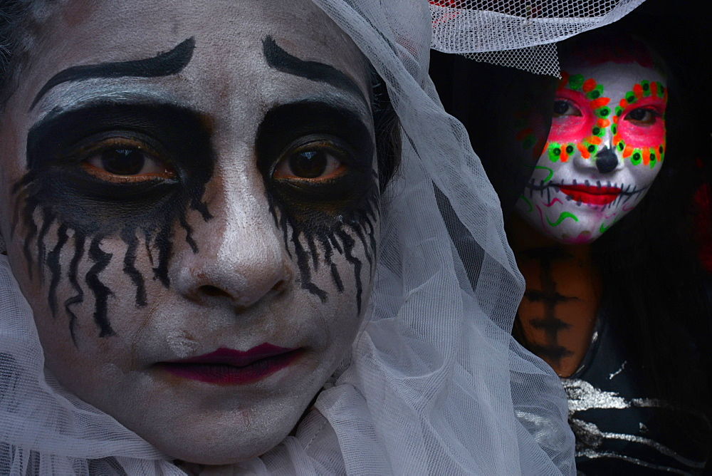 People in costume participating in comparsas or street dances during the Day of The Dead Celebration.